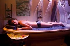 放置轻松的妇女在温泉治疗期间。颜色疗法。 库存图片
