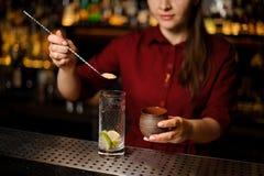 放蔗糖的女性侍酒者入玻璃 免版税库存图片