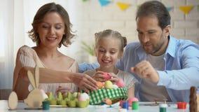 放被洗染的复活节彩蛋入篮子,基督徒传统的美丽的家庭 股票录像