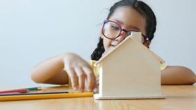 放金钱硬币的亚裔小女孩入房子银行隐喻购买的挽救金钱与四周的房子和房地产概念 股票录像