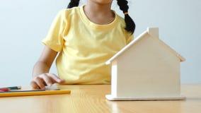 放金钱硬币的亚裔小女孩入购买的清楚的房子银行隐喻挽救金钱与上午的房子和房地产概念 股票视频
