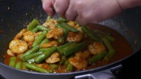 放非洲黑人石灰叶子入平底锅,混乱油煎的虾,围场长豆,香料,咖喱酱 股票视频