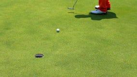 放高尔夫球的慢动作高尔夫球运动员入孔 股票视频