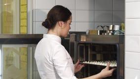 放merengues的年轻美丽的女性糖果商入烤箱 股票录像
