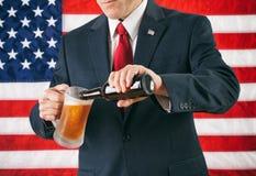 政客:倒冰冷的啤酒的人 库存图片