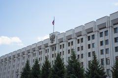 政府大厦,在俄国旗子的屋顶和徽章在翼果的,俄罗斯 在一个晴朗的夏日 免版税图库摄影