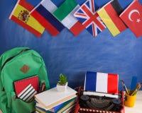 政治,新闻和教育法国的概念-红色打字机,旗子和其他国家,背包,书,文具 免版税库存图片