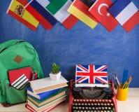 政治,新闻和教育英国的概念-红色打字机,旗子和其他国家,背包,书,文具 库存图片