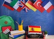 政治,新闻和教育西班牙的概念-红色打字机,旗子和其他国家,背包,书,文具 免版税库存照片