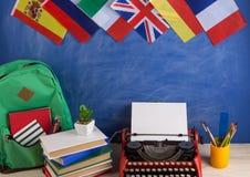 政治,新闻和教育西班牙的概念-红色打字机,旗子,法国、英国和其他国家,背包,书 免版税库存照片