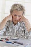 财政问题 在手边倾斜她的头的沮丧的资深妇女,当坐在与票据的桌上和时 库存照片