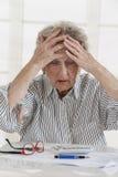 财政问题 在手边倾斜她的头的沮丧的资深妇女,当坐在与票据的桌上和时 库存图片
