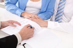 财政顾问解释一个合同-年轻夫妇 免版税库存照片