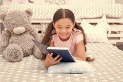 故事概念 愉快的女孩读了有趣故事 小孩ejoy催眠故事在床上 晚安故事 免版税库存图片