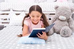 故事概念 愉快的女孩读了有趣的故事 小孩ejoy催眠故事在床上 晚上好故事 免版税库存图片