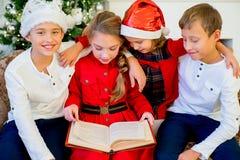 读故事的孩子在圣诞节时间预定 图库摄影