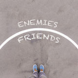 敌人对朋友在沥青地面、脚和鞋子发短信在flo 免版税库存图片