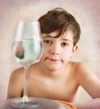 敏锐的青春期前的男孩在水中调查反射行为 库存照片