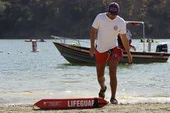 年轻救助者离开湖 在救助艇后 库存图片