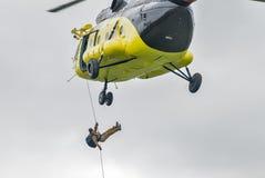 救助者从MI-8直升机登陆由绳索 库存照片