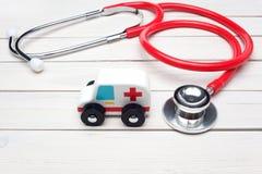 救护车服务概念 救护车在听诊器附近的车玩具在白色木背景 库存照片
