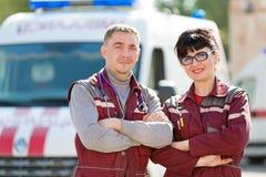 救护车汽车背景的微笑的医务人员 免版税库存照片