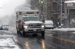 救护车驱动通过在雪风暴的街道 库存照片