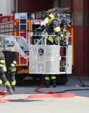 救火梯笼子的消防队员  免版税图库摄影