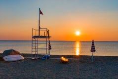 救生员塔海滩日落日出遮阳伞小船 库存图片