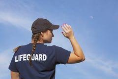 救生员女孩当班在与月亮的蓝天下 免版税库存照片