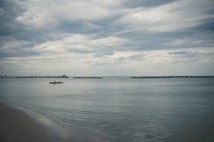 救生员小船在风雨如磐的天空下 免版税库存照片