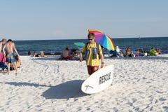救生员沿运载抢救冲浪板的海滩走 免版税库存图片