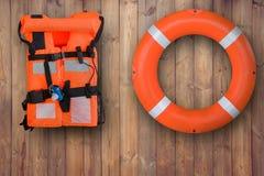 救生圈和垂悬在应急的木墙壁上的救生衣,当下沉的人们浇灌,海,水池 免版税库存照片