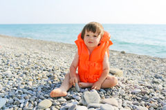 2年救生夹克的儿童坐海边 免版税库存照片