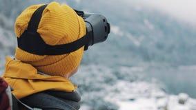 救生服的年轻可爱的人享受虚拟现实玻璃耳机或3d比赛的户外在冬天山