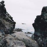 救生艇通过岩石 免版税库存照片