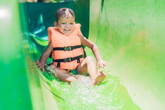 救生衣的一个男孩从一张幻灯片滑下来在水公园 图库摄影