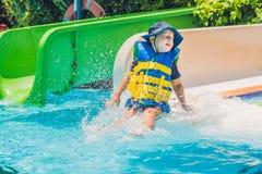 救生衣的一个男孩从一张幻灯片滑下来在水公园 库存图片