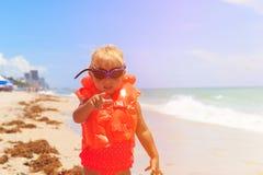 救生衣的逗人喜爱的小女孩把手指指向的观察者 库存图片