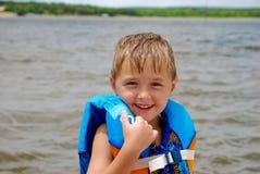 救生衣的逗人喜爱的小男孩在湖 免版税图库摄影