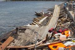 救生衣被放弃的和在口岸的凹下去的土耳其小船 许多难民来自的土耳其小船 免版税库存图片