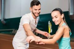 教一个少妇的专业正面辅导员打网球 免版税库存照片