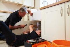 教一位年轻学徒的水管工修理厨房水槽 免版税库存照片