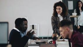 教两位黑人男性经理的愉快的专业年轻可爱的企业辅导者妇女在现代顶楼办公室桌上 股票录像
