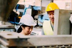 教亚裔女性学徒的年轻亚裔男性工厂劳工 库存图片