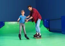 教他儿子滑旱冰的父亲 图库摄影