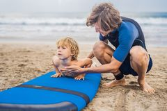 教他四岁的儿子如何的父亲或辅导员冲浪  免版税库存照片