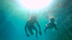 教他的儿子如何的父亲的Ultrahd慢动作水下的射击游泳在水池 小孩男孩和他的父亲下潜 股票视频