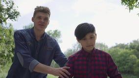教他的儿子的可爱的年轻父亲乘坐滑行车在公园 人支持孩子,帮助他保持 影视素材