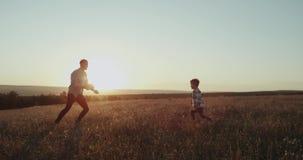 教他的儿子的爸爸打网球在自然,令人惊讶的日落 股票录像
